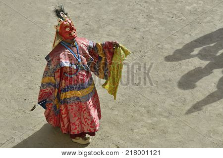 Buddhist monk in festive red clothes and red ritual mask Mahakala in the courtyard of the monastery, tantric ritual, Tibet.