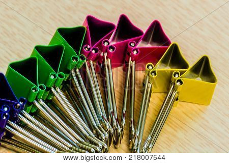 Collection of colorful paperclips standing on edge on a brown wood grained table top