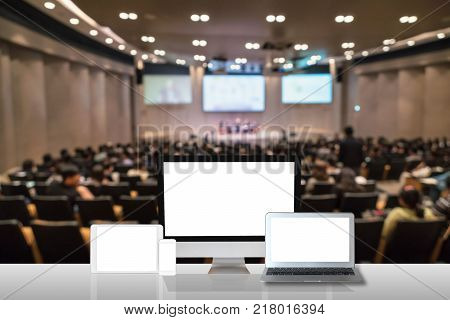 Computer set show on the white table over the Abstract blurred photo of conference hall or seminar room with attendee background business technology and education concept