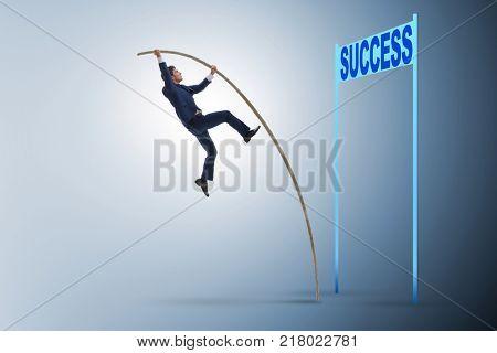 Businessman pole vaulting over towards his success career
