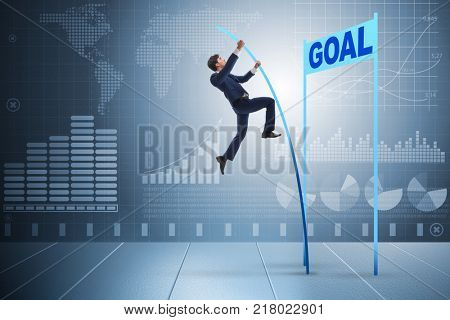 Businessman pole vaulting towards his goal in business concept