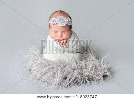 Newborn girl wrapped in blue wrap