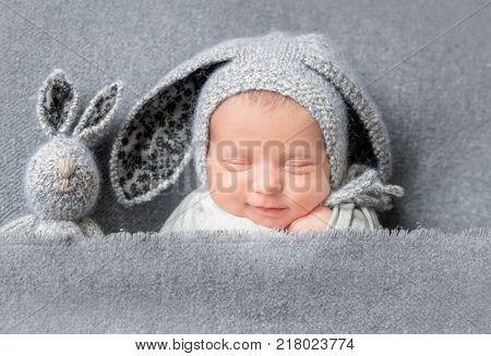 Infant baby boy sleeping under blanket