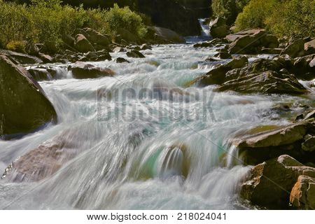 Stormy and frothy mountain stream. Source famous Krimml waterfalls in Austria. Pastoral in the Alpine mountain valley