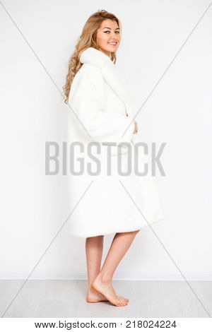 Blonde woman in white fur coat, full length portrait isolated on white wall