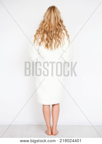 Back view, Beautiful young woman in white fur coat. Isolated on white wall background