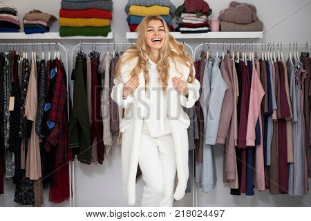 Young beautiful blonde woman in white fur coat in show room