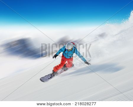 Young man snowboarder running downhill in fast motion blur effect, Alpine mountains. Winter sport and recreation, leasure outdoor activities.