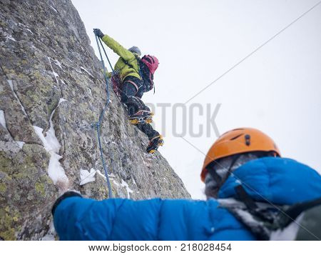Mountaineers on an extreme winter climb. West Alps, Europe. Concepts: risk, strength, courage, teamwork.