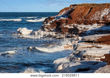 Winter waves roll in along the shoreline of rural Prince Edward Island, Canada. poster