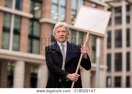Grey-haired businessman showing protest banner while expressing his attitude