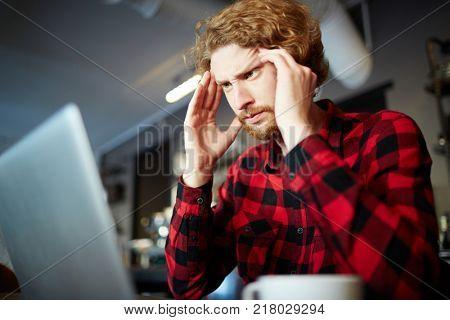 Young businessman concentrating on work while looking at laptop display