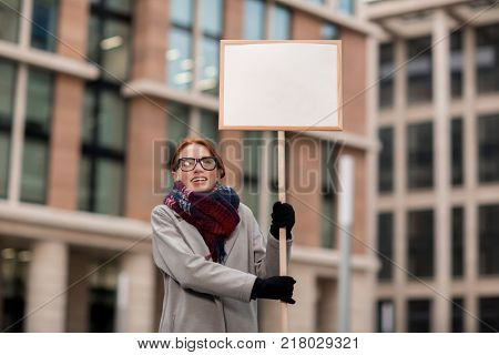 Young woman with protest placard expressing her attitude towards social unjustice
