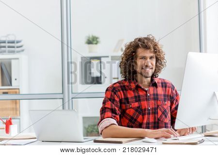 Happy young designer or architect sitting in front of computer monitor and doing his work in office