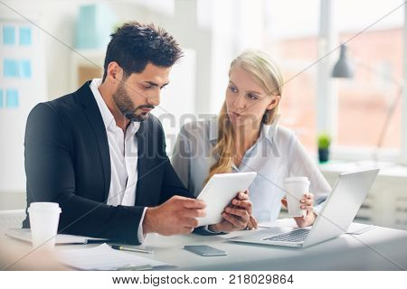 Confident analyst with touchpad reading online data in the net with young colleague near by