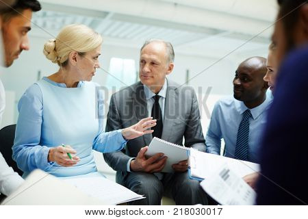 Two mature financiers discussing report of one of them among their young intercultural colleagues at meeting