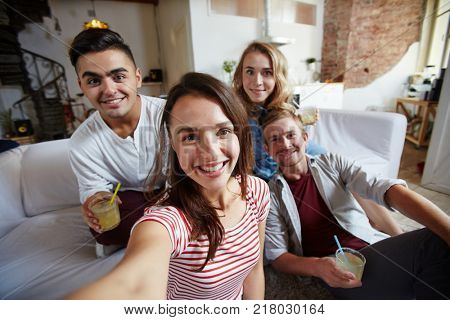 Happy girl and her friends looking at camera with smiles while making selfie