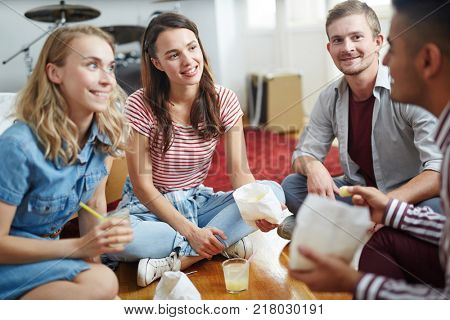 Happy friends with snack sitting on the floor and listening to one of guys curious story