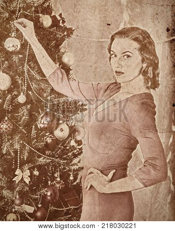 Nostalgy Christmas woman dressing Xmas tree. Woman hangs up last decoration ball . She turns her face and looking at camera. Home portrait vintage sepia old retro photo 1910-1940.