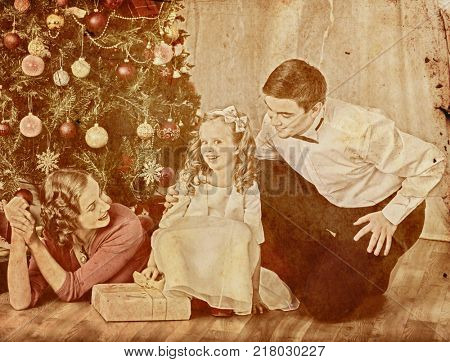 Nostalgy Christmas family with child girl dressing Christmas tree. Xmas tree presents for happy people. Home portrait vintage sepia old retro photo 1910-1940.