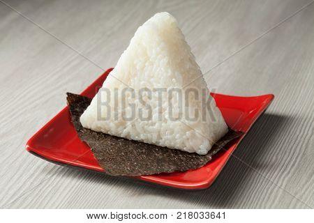 Fresh made Japanese triangular onigiri on seaweed on a dish