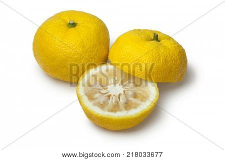 Pair of fresh yellow whole and half Japanese Yuzu on white background