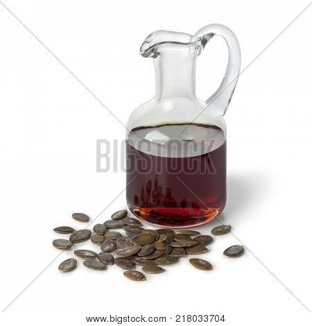 Bottle with pumpkin seed oil and roasted seeds on white background