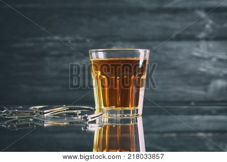 Glass and handcuffs on table. Alcohol dependence concept