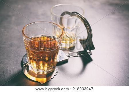 Glasses with handcuffs on grey background. Alcohol dependence concept