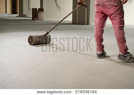 Manual worker pressing vinyl floor with pust roller.