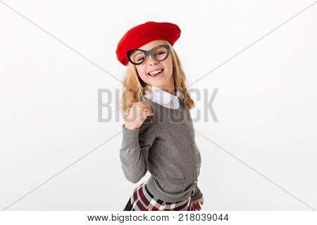 Portrait of a smiling little schoolgirl dressed in uniform grimacing and looking at camera isolated over white background