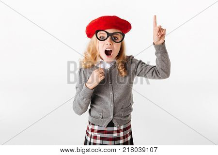 Portrait of an excited little schoolgirl dressed in uniform grimacing and pointing finger up isolated over white background