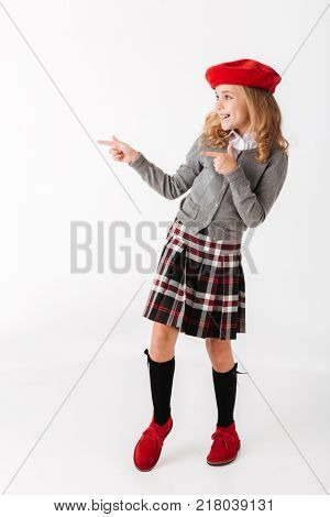 Full length portrait of a cheery little schoolgirl dressed in uniform standing and pointing fingers away at copy space isolated over white background