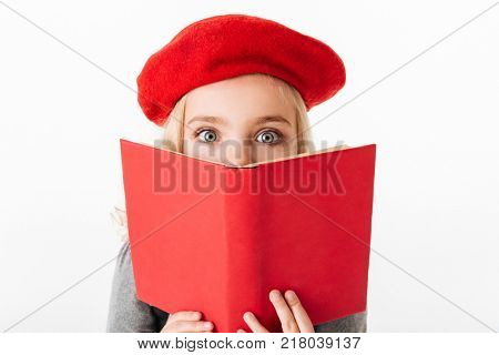 Close up portrait of a cute little schoolgirl dressed in uniform holding book at her face and looking at camera isolated over white background