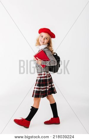 Full length portrait of a cute little schoolgirl dressed in uniform with backpack holding book while walking and looking at camera isolated over white background