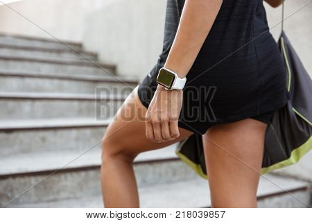 Close up of a woman dressed in sportswear carrying bag while walking up the steps outdoors