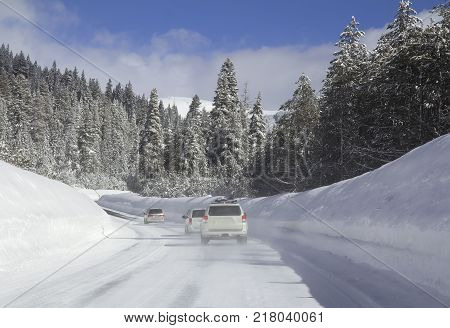 Winter landscape with cars on the road in fthe snowy forest.