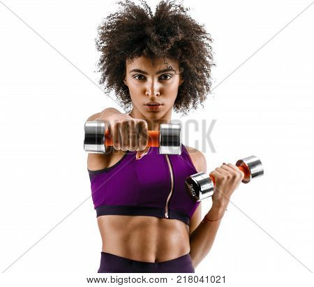 Sporty girl doing boxing exercises making direct hit with dumbbells. Photo of african girl on white background. Strength and motivation