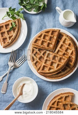 Whole wheat savory breakfast viennese waffles cream and milk on blue background top view