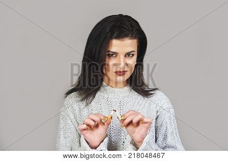 woman holding broken cigarette . The concept of a healthy lifestyle and anti-Smoking