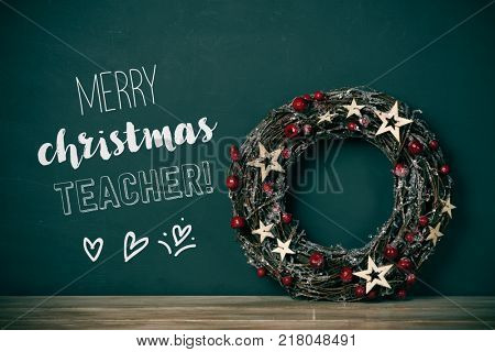 a nice christmas wreath with red fruits and golden stars, and the text merry christmas teacher in a green chalkboard