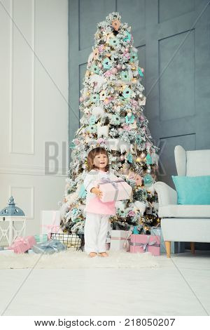 Children's delight. Little two-year-old girl is happy near the Christmas tree. New Year is soon