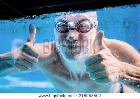Senior man swimming underwater in an indoor swimming pool. Active pensioner enjoying sport. Thumbs up gesture.