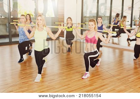 Group of young women in fitness class. People making exercises. Girls do lunges with barbells. Healthy lifestyle, intensive fitness training