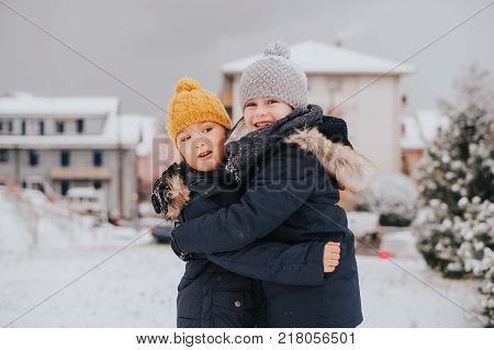 Outdoor portrait of young 6 year old boys wearing warm jacket and boots enjoying winter time
