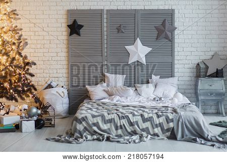 The bedroom decorated for Christmas. Cozy gray home interior. New year decoration. bright bedroom room with large double bed. Christmas tree with shyning garland