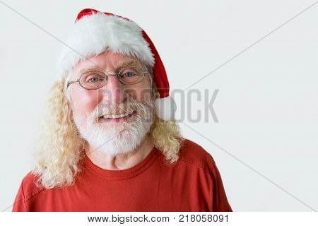 Portrait of happy Santa Claus. Studio shot of cheerful old man in Christmas hat. Face of elderly smiling man celebrating Christmas
