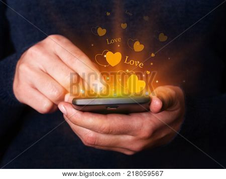 Woman hands holding and using smartphone mobile or cell phone for texting or messaging for Valentines Day. Concept for love, passion, online dating or romance.