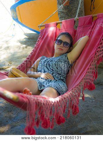 young pretty happy Asian Chinese woman lying lazy on beach hammock sun bed relaxed and cheerful in Summer holiday trip enjoying vacation in tourism and travel concept