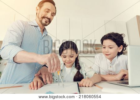 Easy maths. Happy positive clever man holding a pair of compasses and smiling while helping his kids with maths homework